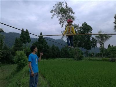 在张禹的训练下,望望戴着安全帽,端着竹竿,在河堤钢丝上行走。 小圆图为望望喝酒视频截图